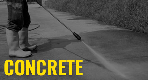 construction worker spraying a new concrete surface